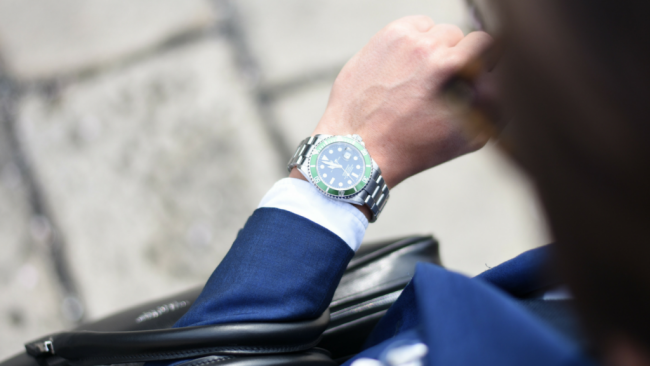 wealthy man looks at watch for time