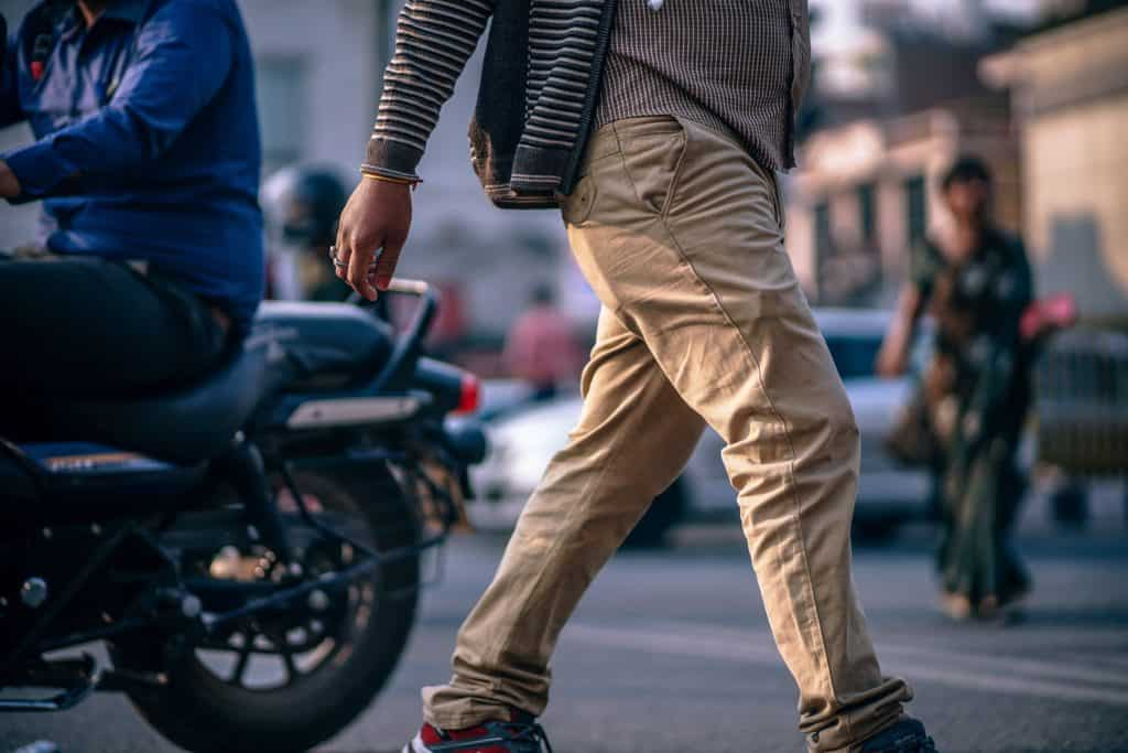 Man's pant legs walking on street