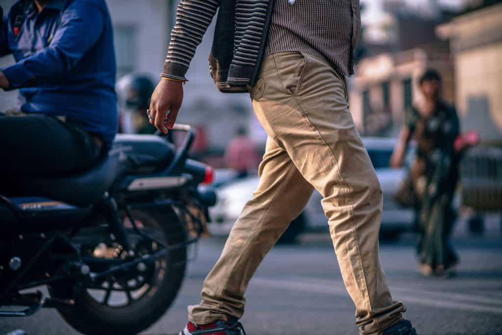 Man's pant legs walking on street