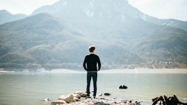 man standing on rock contemplating failure