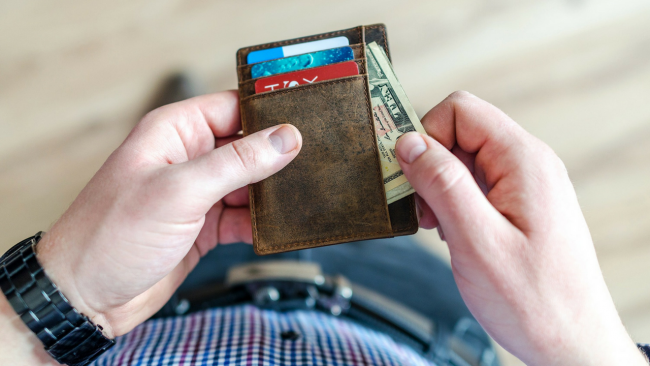 man looking at wallet to not overspend