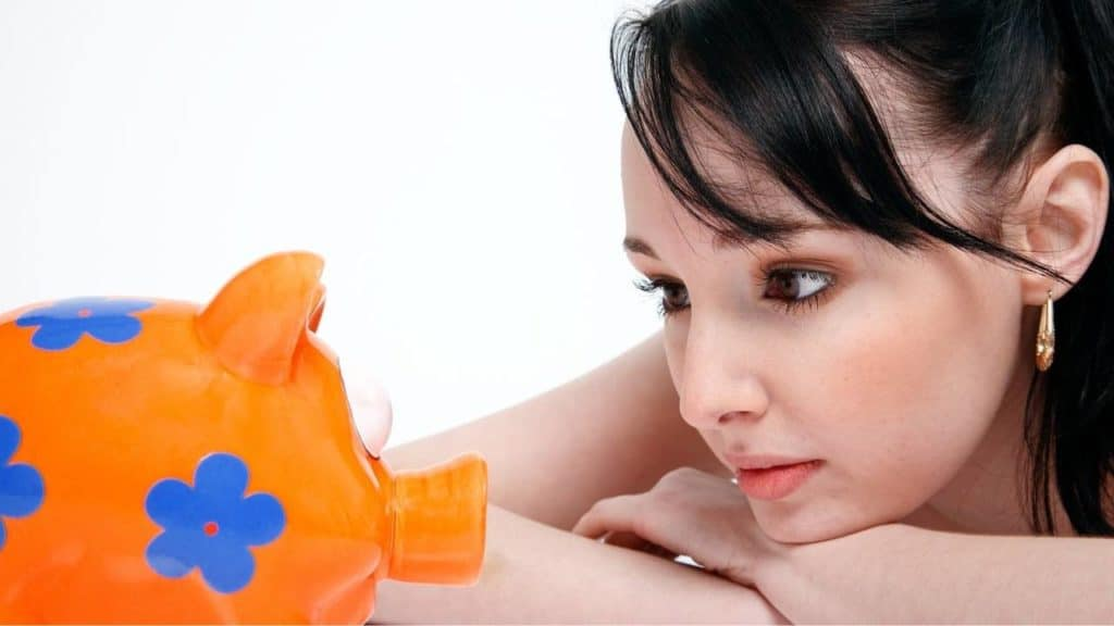 a woman looking at a piggy bank
